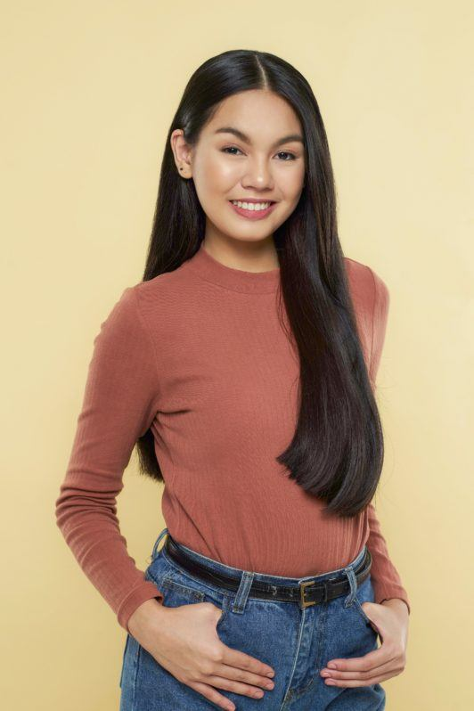 Nine strand braid: Asian woman wearing brown long sleeved shirt and denim pants with long black hair standing against yellow background