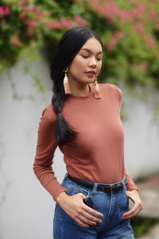 Nine strand braid: Asian woman wearing a brown long-sleeved shirt and denim pants with long black hair in braids in an outdoor location