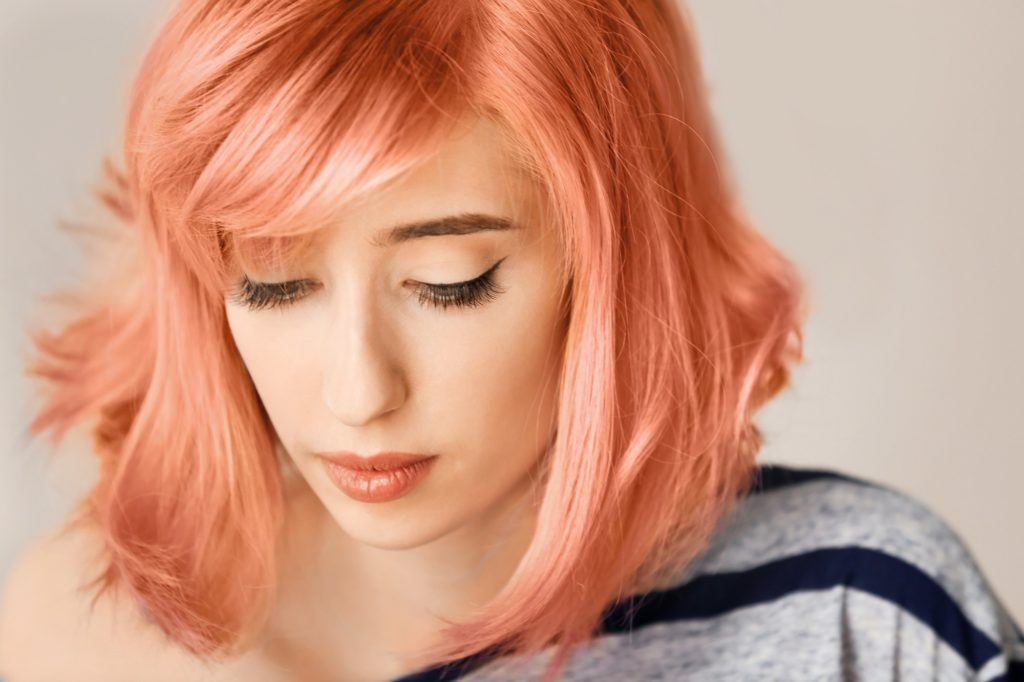Orange hair: Closeup shot of a girl with apricot hair against a light gray background