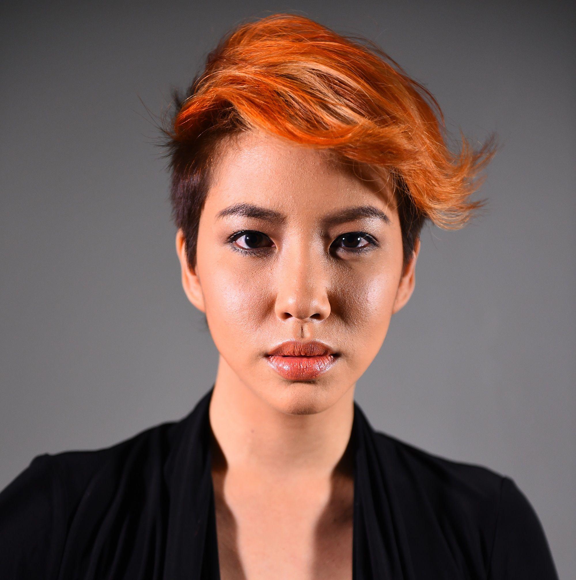 Orange hair: Closeup shot of a woman with orange pixie cut wearing a black blouse