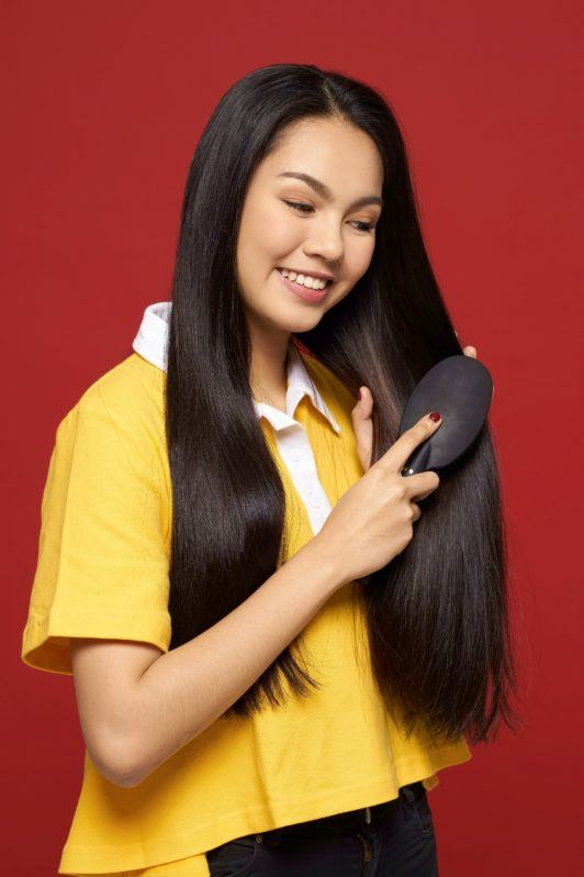 Rope braid: Asian woman with long black hair wearing a yellow shirt brushing her hair against a red background