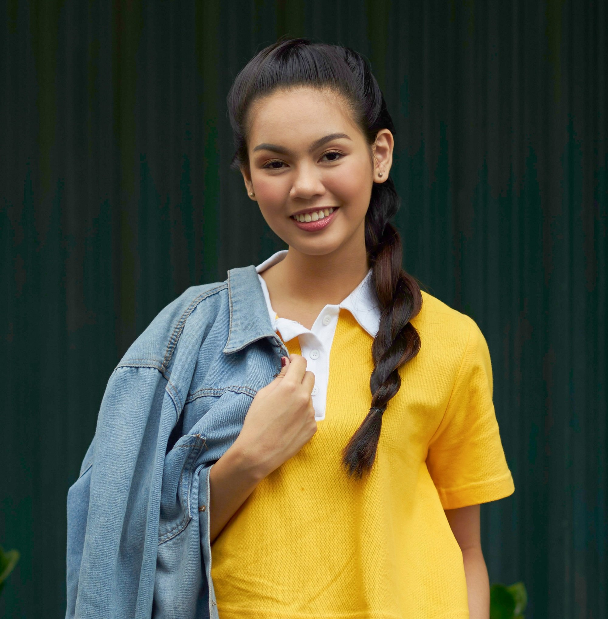 Rope braid: Asian woman with long black hair in a rope braid wearing a yellow shirt outdoors
