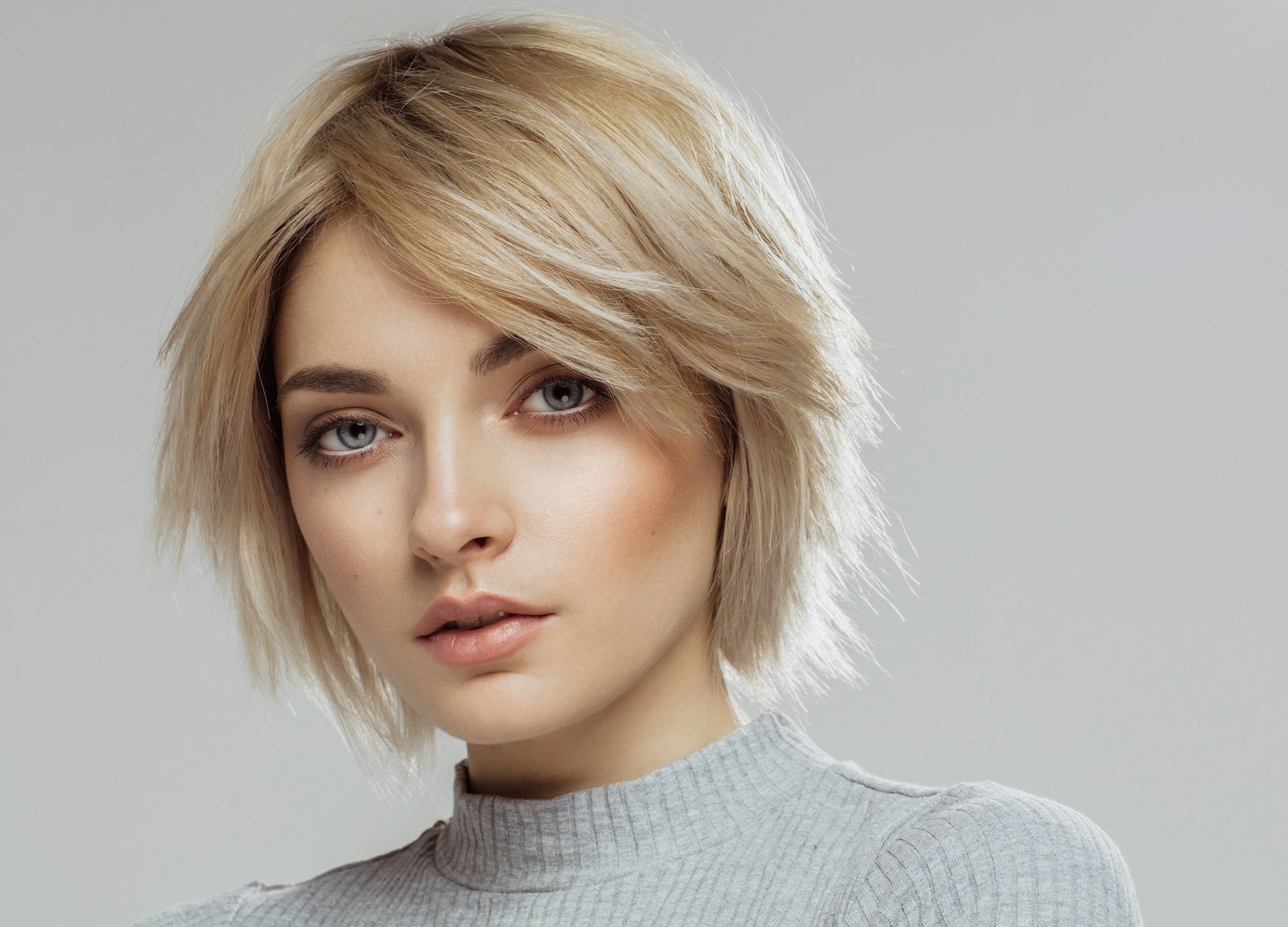 Short blonde hair: Closeup shot of a woman with short layered blonde hair wearing a gray top against a gray background