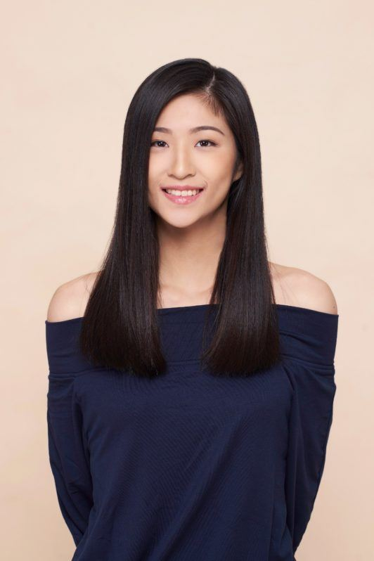 Side ponytail: Asian woman wearing a dark blue blouse with long black hair standing against an oyster-colored background