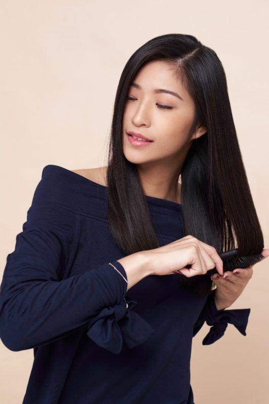 Side ponytail: Asian woman wearing dark blue blouse brushing her long black hair and standing against an oyster-colored background