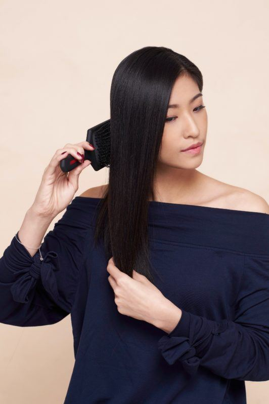 Side ponytail: Asian woman wearing a dark blue blouse brushing her long black hair and standing against an oyster-colored background