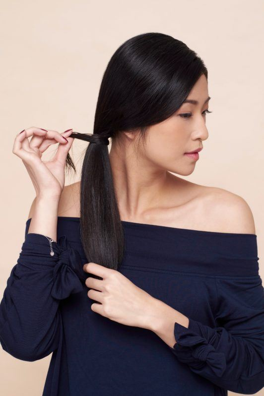 Side ponytail: Asian woman wearing a dark blue blouse putting her hair in a side ponytail