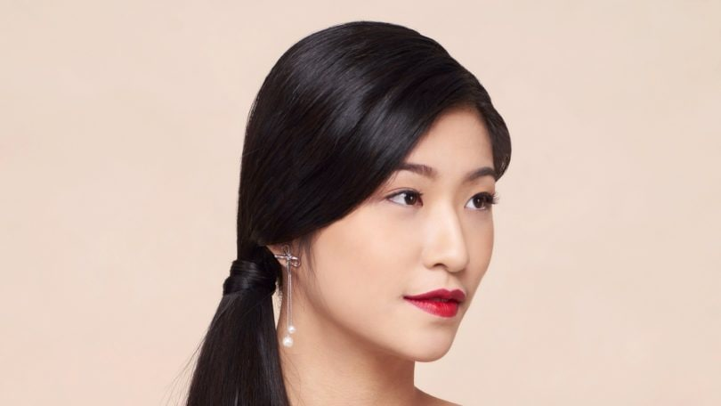 Side ponytail: Asian woman wearing dark blue blouse with long black hair in side ponytail against an oyster-colored background