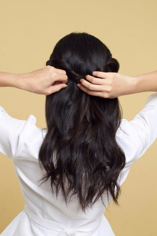 Twisted ponytail half updo: Back shot of an Asian woman styling her long black hair wearing a white blouse