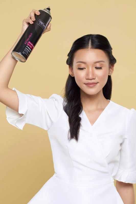 Twisted ponytail half updo: Asian woman spritzing hairspray on her long black hair and wearing a white blouse against a yellow background