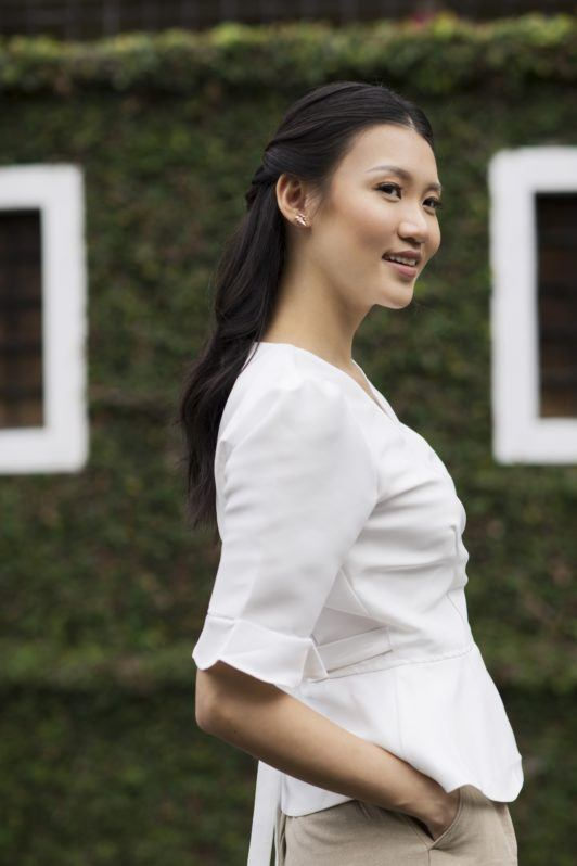 Twisted ponytail half updo: Side view of an Asian woman with long black hair and wearing a white blouse outdoors