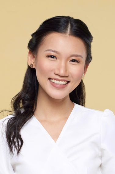 Twisted ponytail half updo: Closeup shot of an Asian woman with long black hair wearing a white blouse against a yellow background