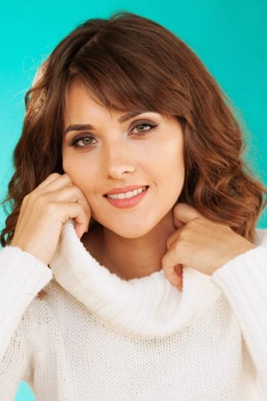 Best haircuts for different face shapes: Closeup shot of a woman with wavy lob with wispy bangs wearing a white turtleneck top