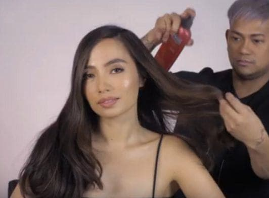 Chic twisted ponytail: Filipina woman with long black hair being sprayed with heat protectant