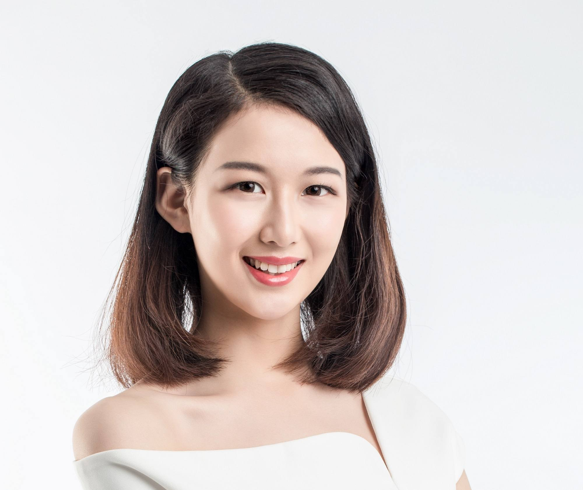 Chocolate brown hair: Closeup shot of an Asian woman with long dark bob wearing a white dress against a white background