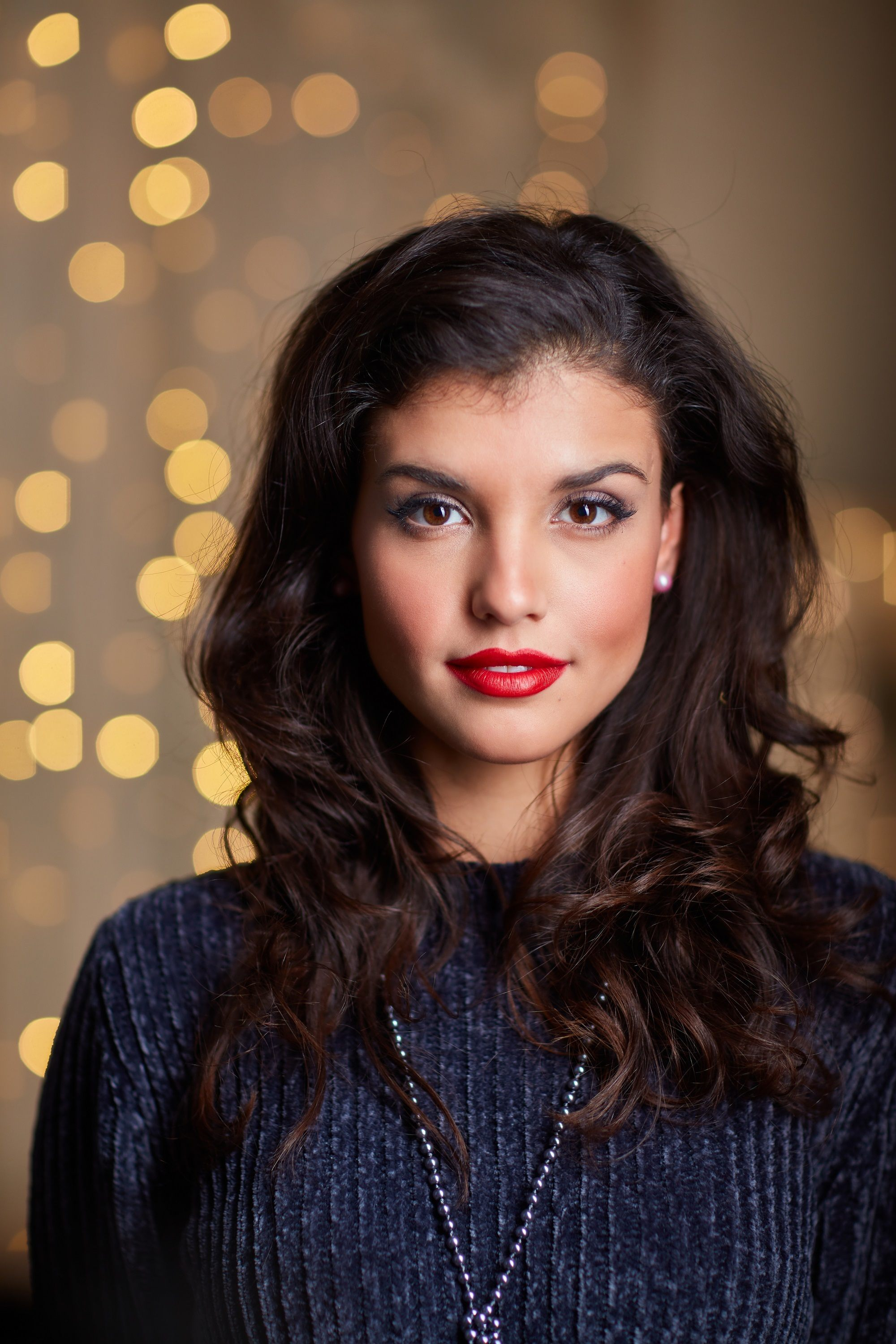 Christmas hairstyles: Closeup shot of a woman with dark wavy hair wearing dark blue blouse with Christmas lights at the background