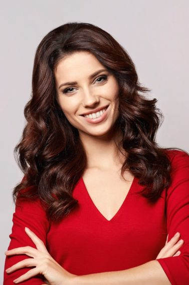 Christmas hairstyles: Woman with long dark brown curly hair wearing a red blouse against a light gray background