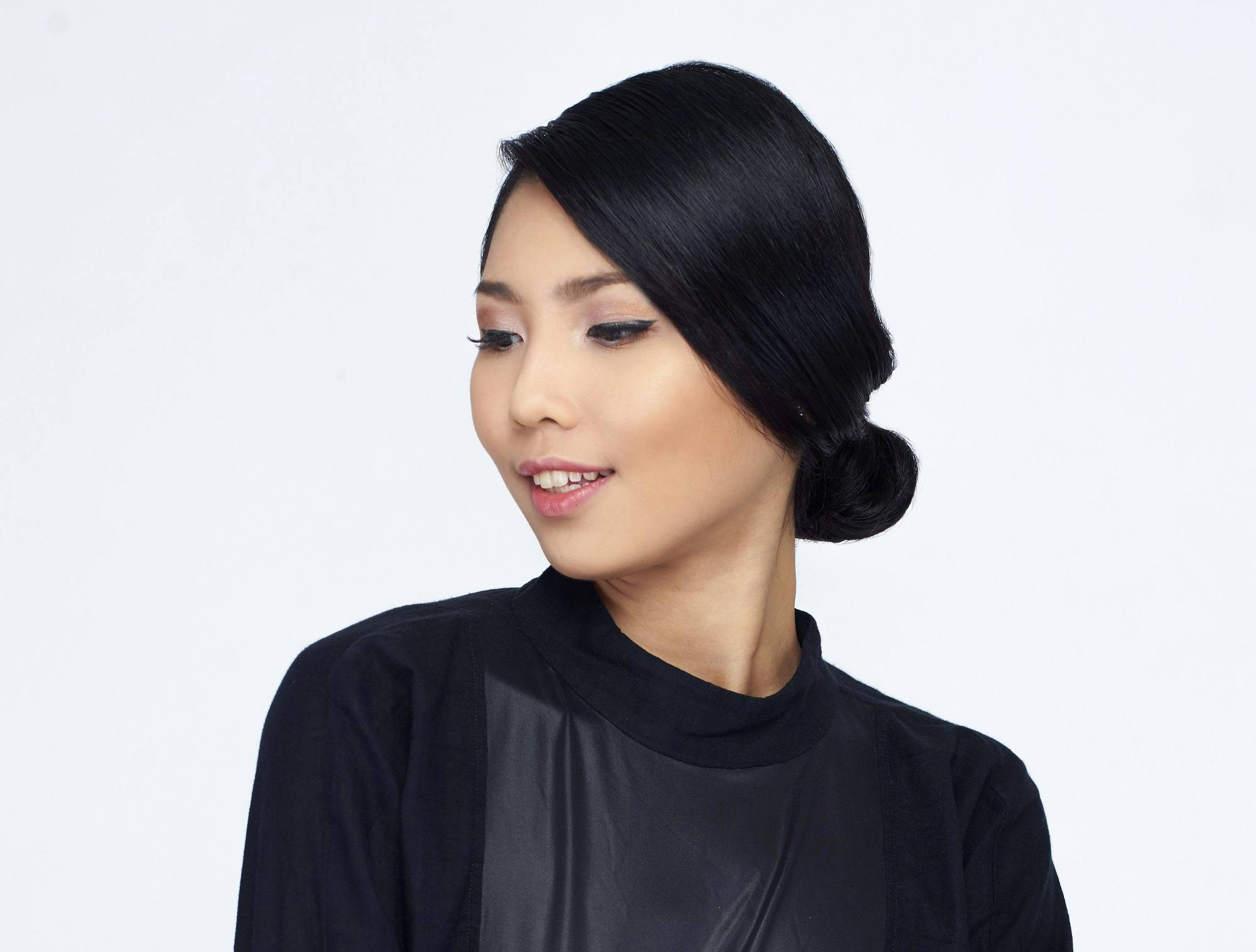 Christmas party hairstyles: Closeup shot of an Asian woman with black hair in chignon wearing a black dress