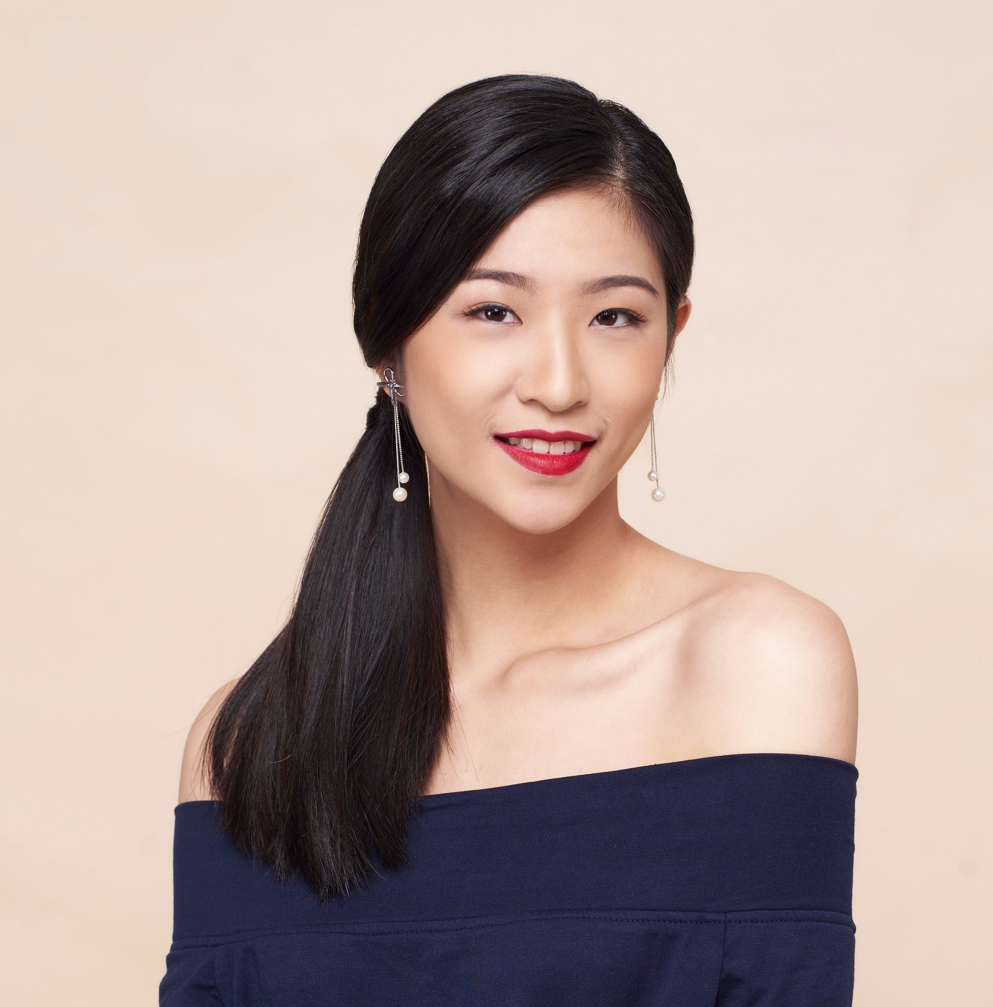 Christmas party hairstyles: Closeup shot of an Asian woman with long black hair in side ponytail wearing a dark blue off-shoulder blouse