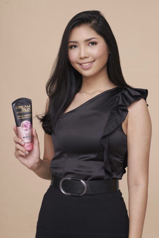 Cream Silk Triple Keratin Rescue Ultimate Straight Glamorously Straight Hair: Asian woman with long black hair wearing black top and skirt holding a Cream Silk conditioner