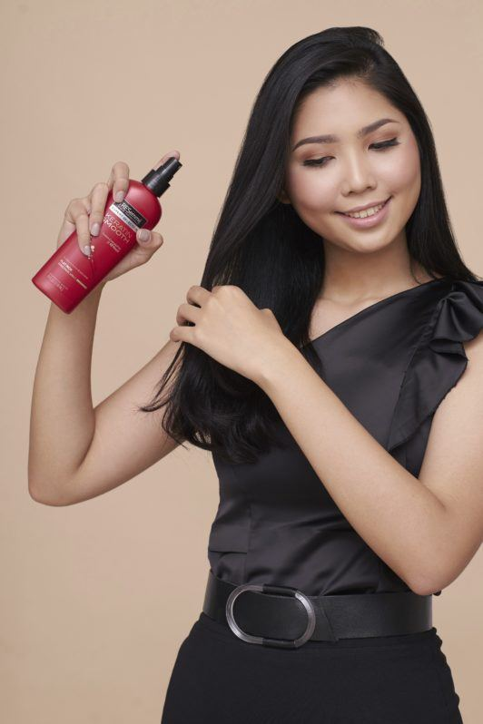 Cream Silk Triple Keratin Rescue Ultimate Straight Glamorously Straight hair: Asian woman with long black hair wearing black top and skirt spraying heat protectant on her hair