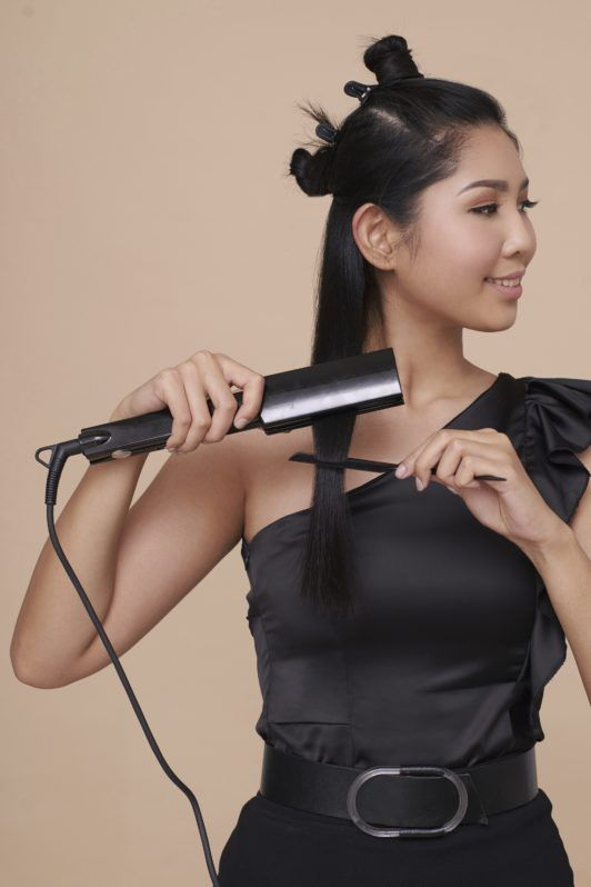 Cream Silk Triple Keratin Rescue Ultimate Straight Glamorously Straight Hair: Asian woman straightening her long black hair and wearing black top and skirt against an oyster-colored background