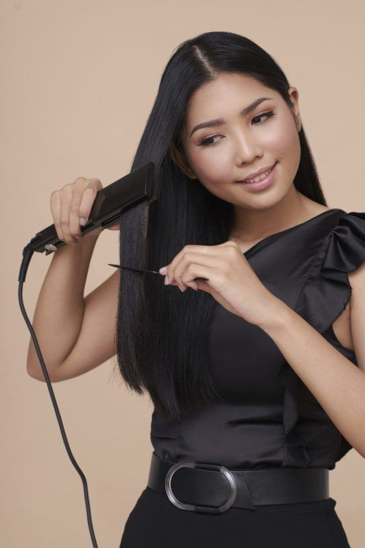 Cream Silk Triple Keratin Rescue Ultimate Straight Glamorously Straight Hair: Asian woman wearing black top and skirt straightening her long black hair