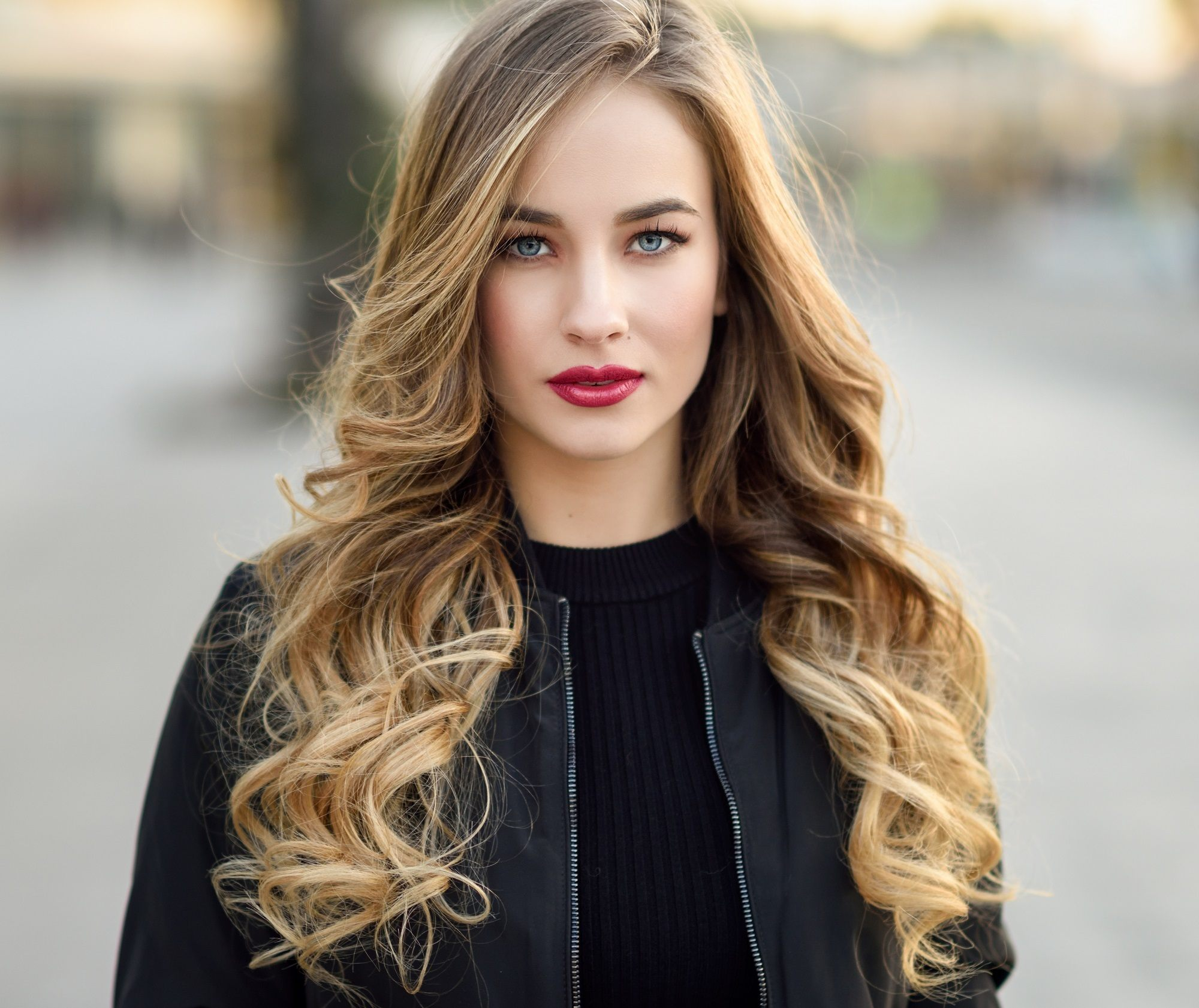 Curly blonde hair: Closeup shot of a woman with long bronde curly hair wearing black long sleeved-top outdoors