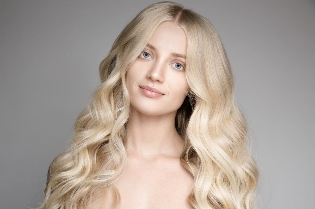 Curly blonde hair: Closeup shot of Caucasian woman with long curly blonde hair against a gray background