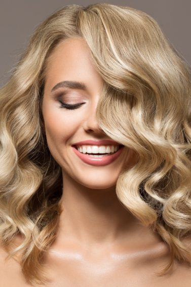 Curly blonde hair: Closeup shot of Caucasian woman with curly blonde hair against a gray background