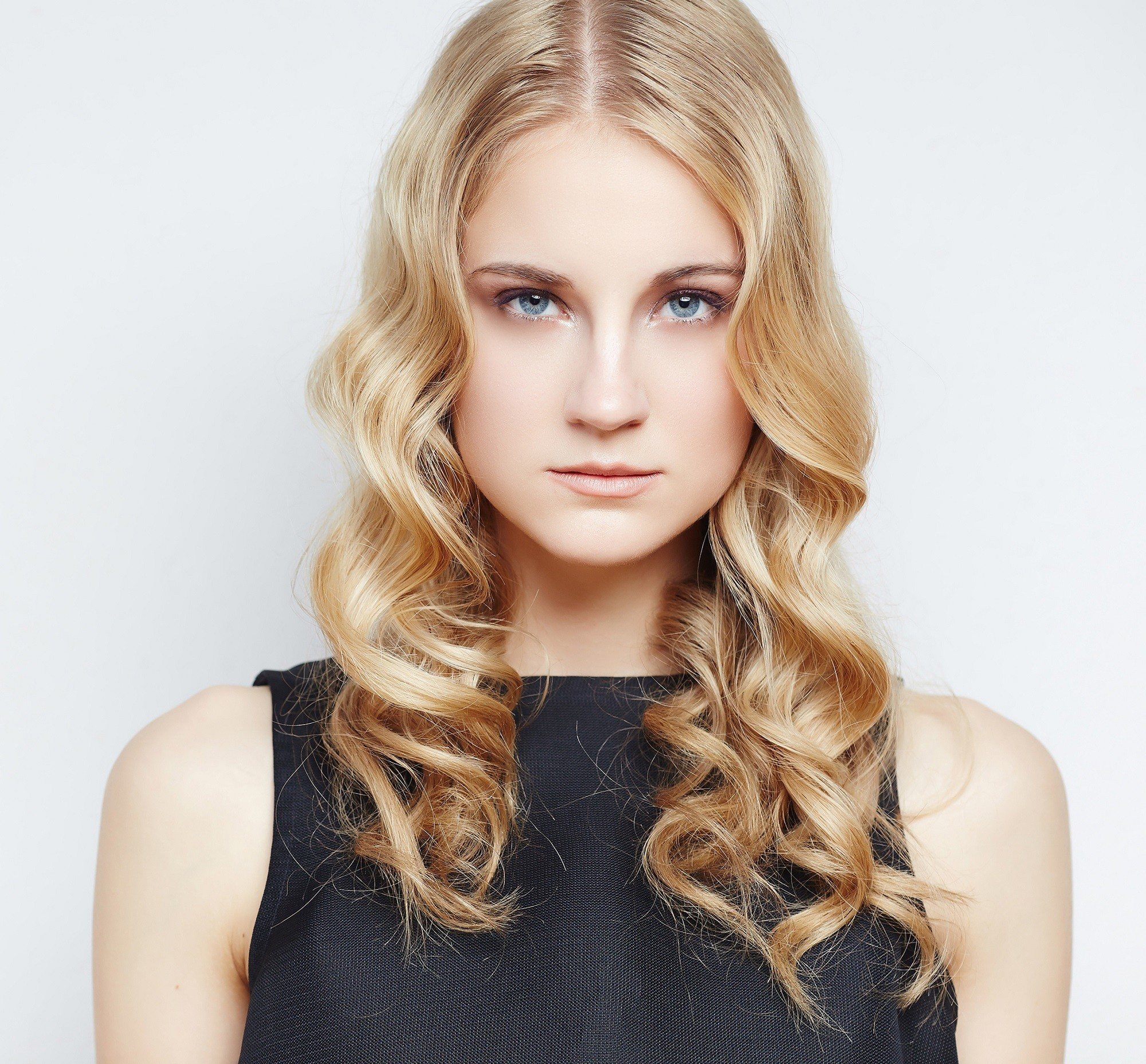 Curly blonde hair: Closeup shot of Caucasian woman with long curly strawberry blonde hair wearing black sleeveless top against a white background