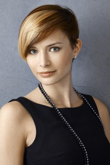 Elegant hairstyles for short hair: Woman with a blonde pixie cut wearing a black sleeveless top