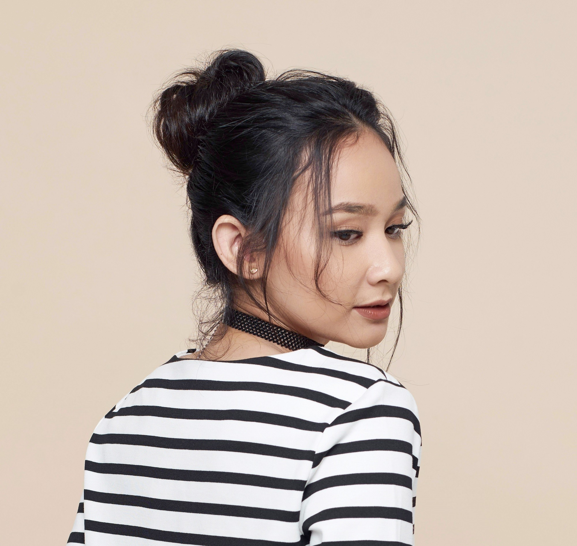 Frizy hairstyles: Closeup shot of an Asian woman with long black hair in a messy bun