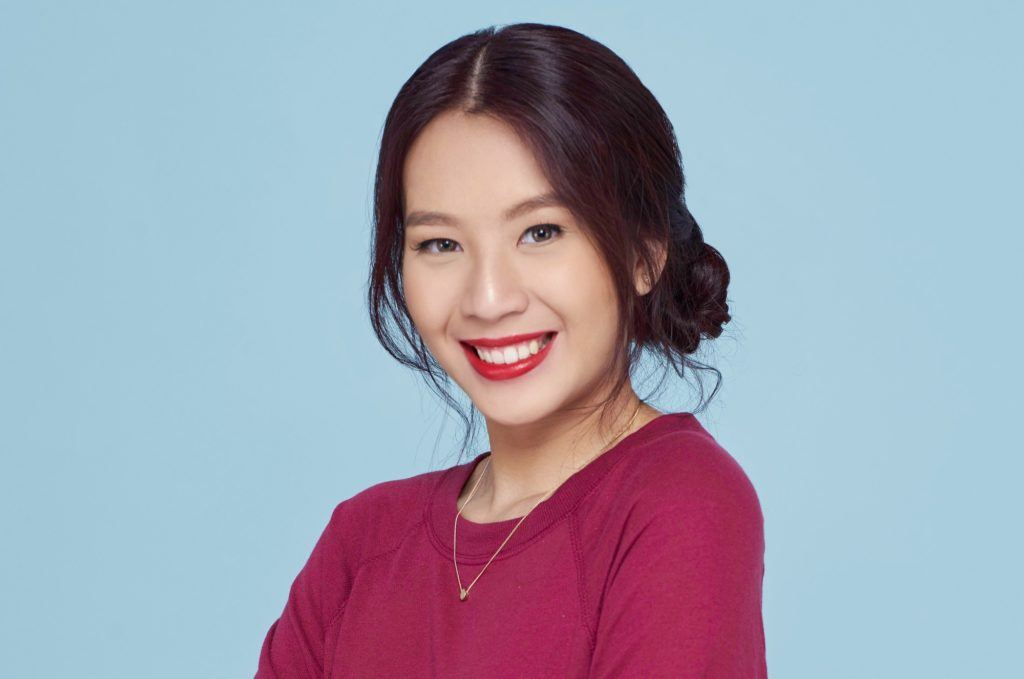 Get the look holiday hairstyles: Closeup shot of an Asian woman with black hair in a banana bun wearing fuchsia sweater against a blue background
