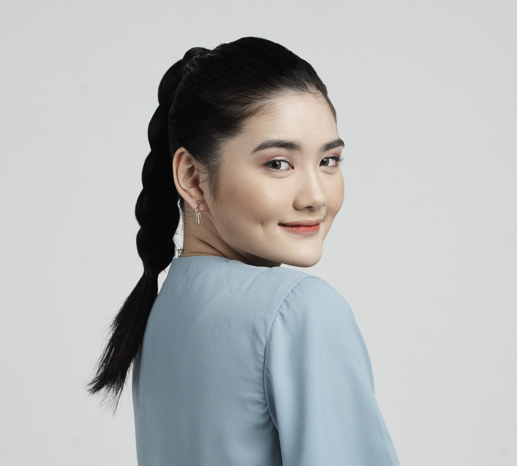 Get the look holiday gift boxes: Closeup shot of an Asian woman with long black hair in braid ponytail wearing a blue dress against a light gray background