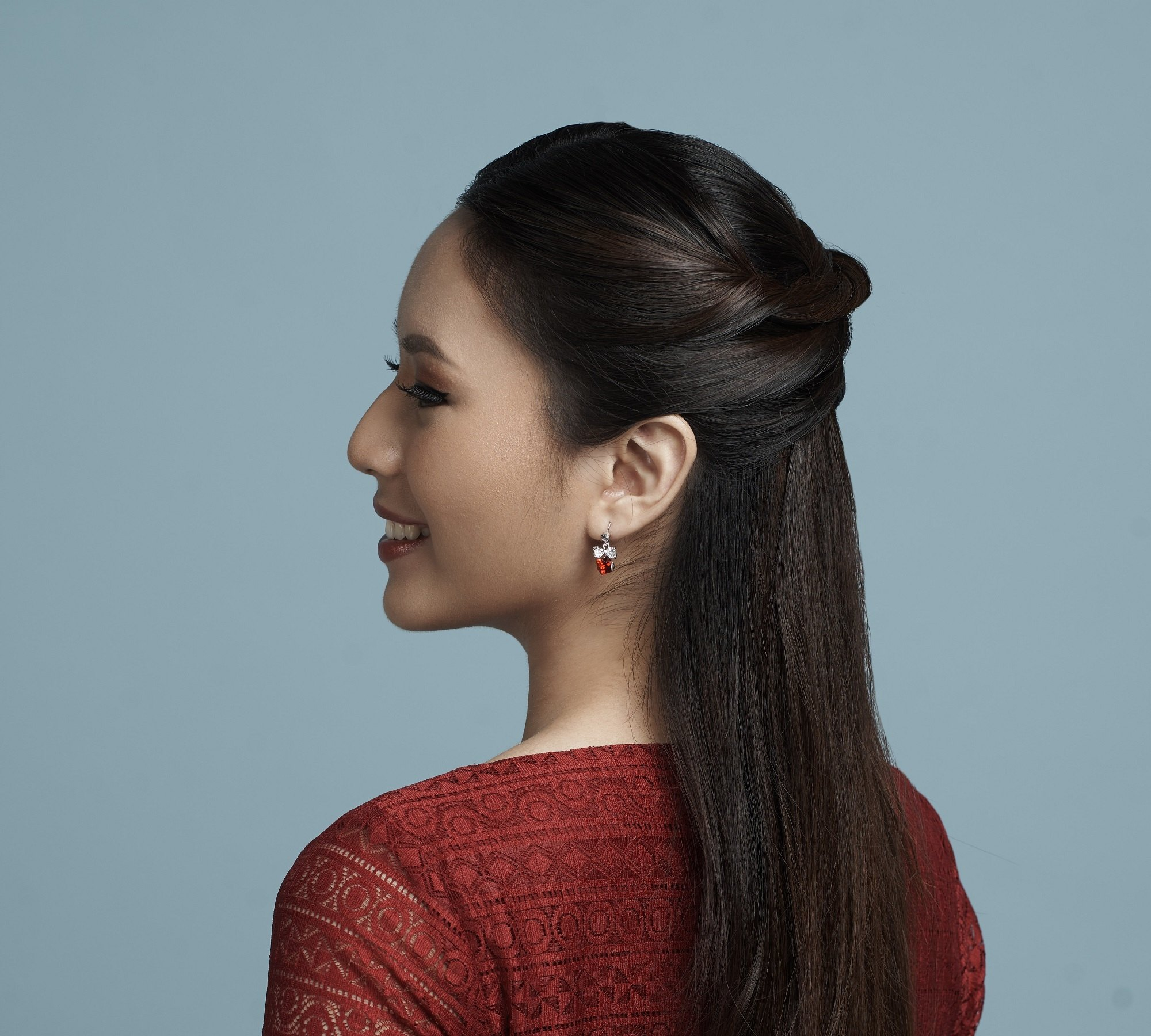 Get the look holiday gift boxes: Closeup shot of an Asian woman with long black hair in curly ponytail against a champagne background