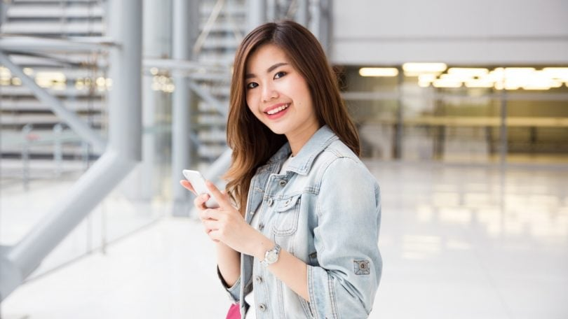 Hair care tips for traveling: Asian girl with long dark hair wearing a denim jacket smiling in the airport
