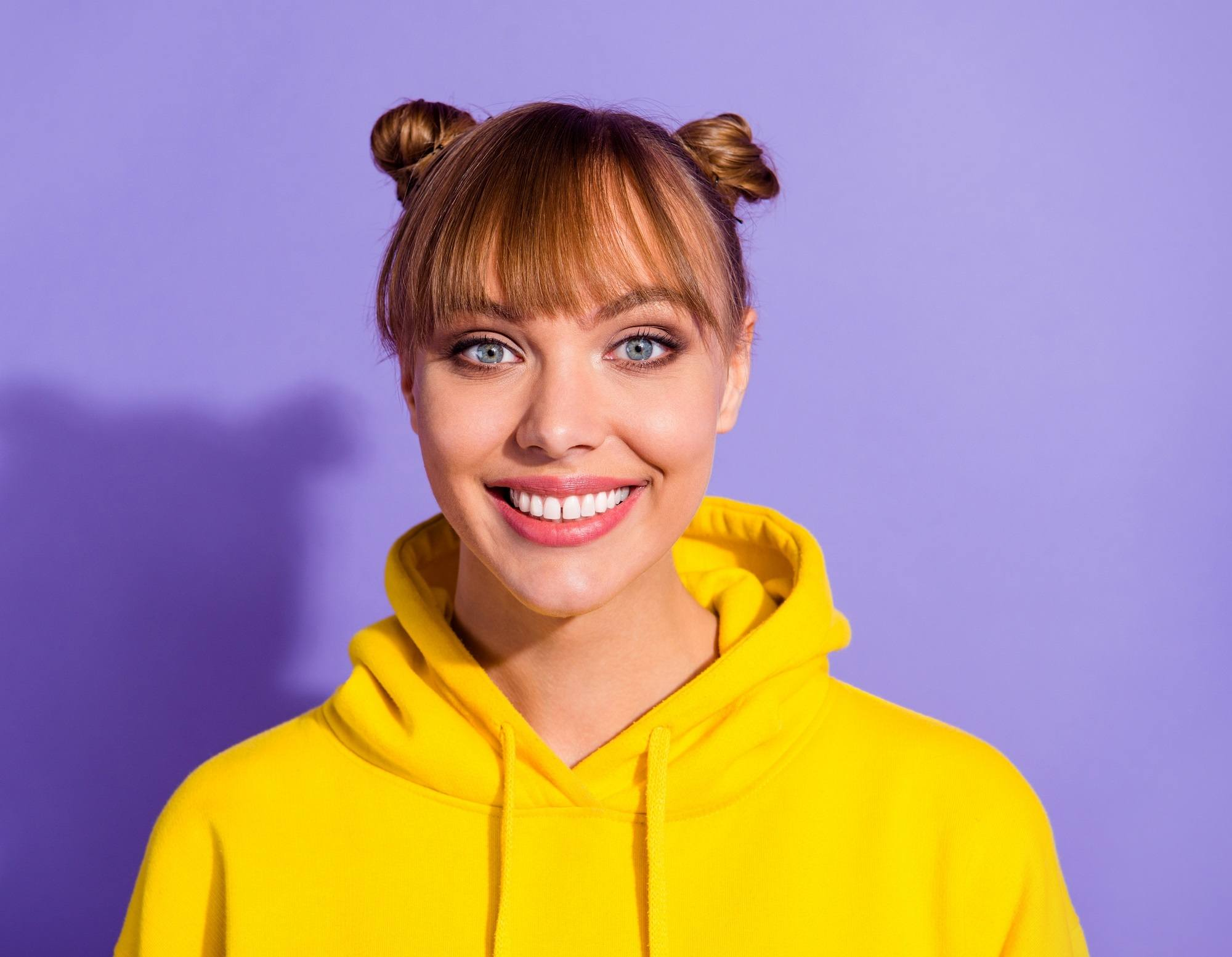 Hair trends to try in 2019: Closeup shot of a woman with blonde hair in double buns wearing a yellow jacket