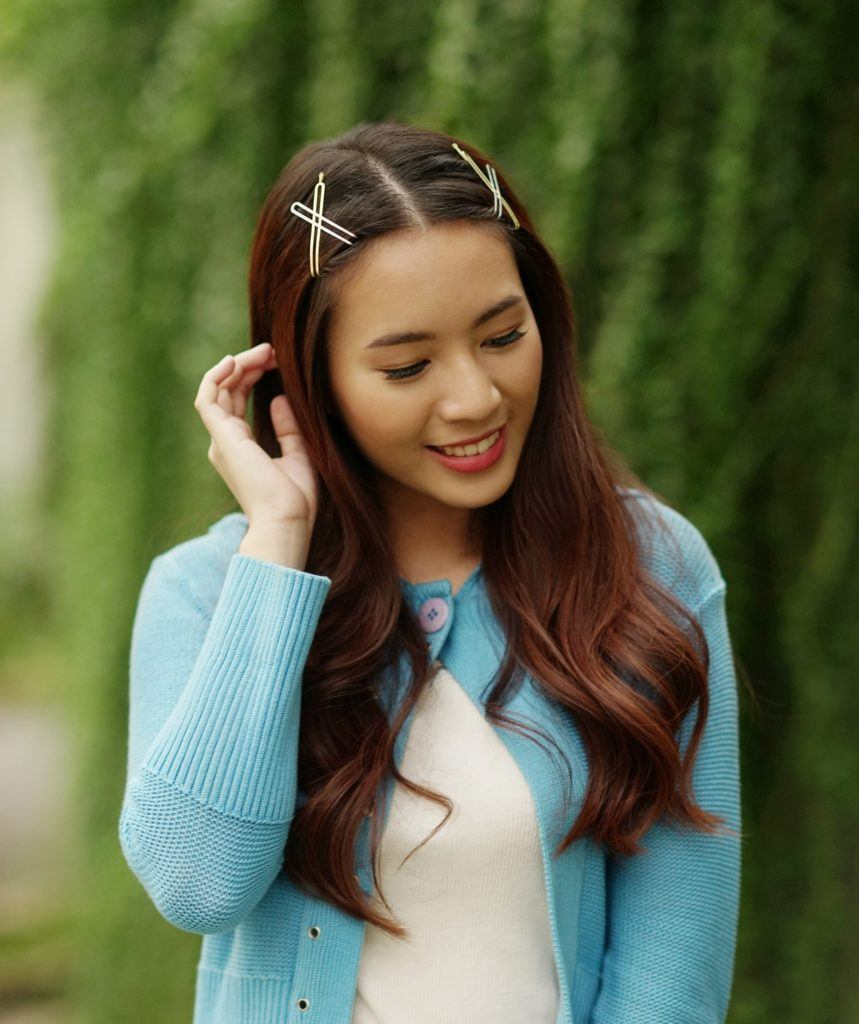 Hair trends to try in 2019: Woman with long dark hair with hair clips wearing a blue cardigan outdoors