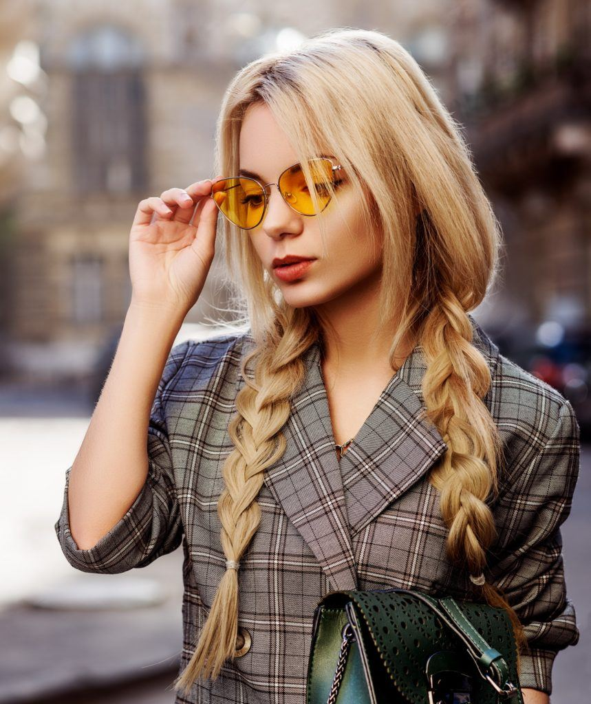 Hair trends to try in 2019: Woman with long blonde hair in two braids wearing a plaid coat and sunglasses outdoors