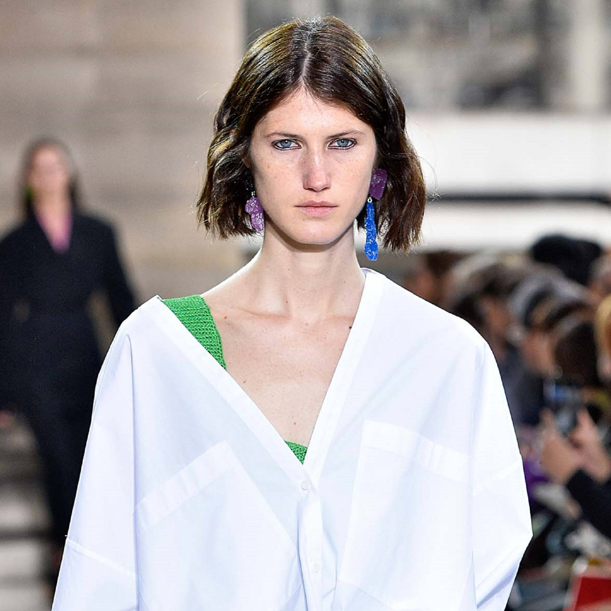Hair trends to try in 2019: Woman with dark brown bob wearing a white blouse on the runway