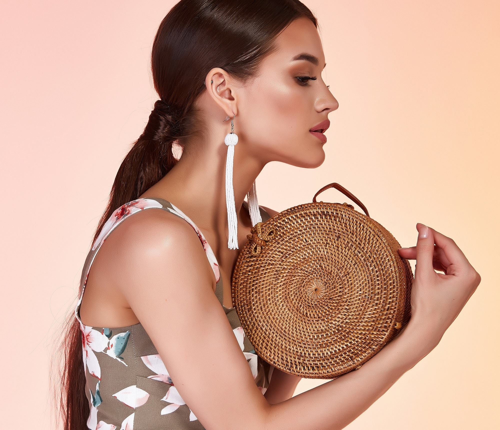 Hair trends to try in 2019: Side view shot of a woman with long dark hair in a low ponytail wearing a sleeveless top and dangling earrings