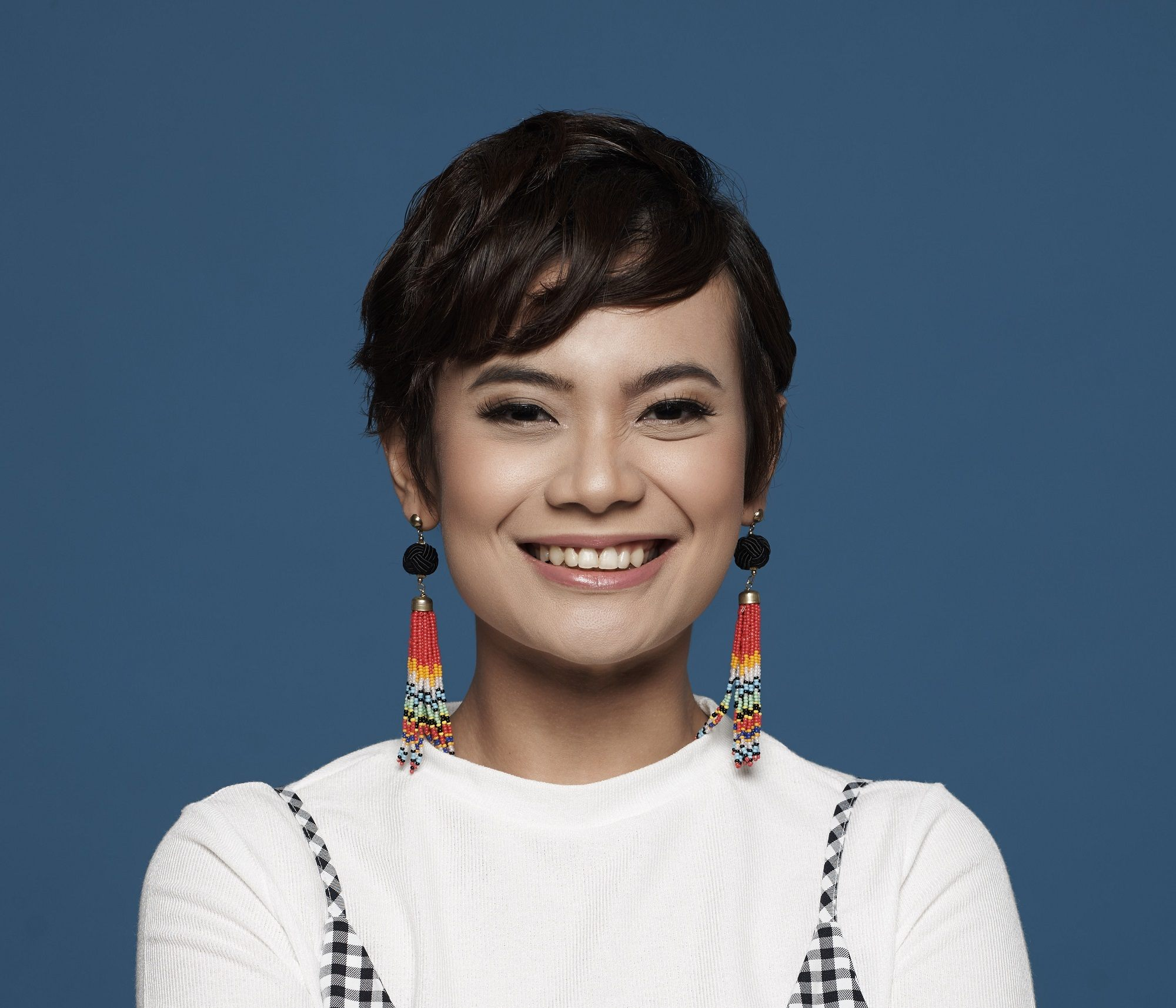 Hair trends to try in 2019: Closeup shot of an Asian woman with dark tousled pixie cut and dangling earrings