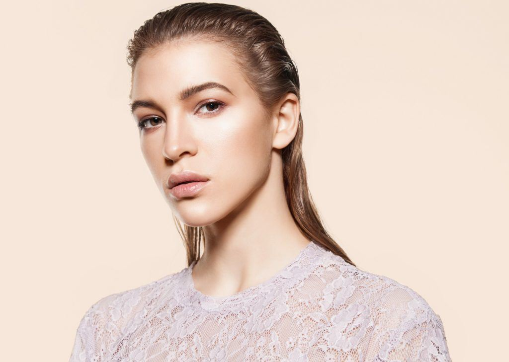 Hair trends to try in 2019: Closeup shot of a woman with slicked back wet blonde hair wearing a light pink shirt