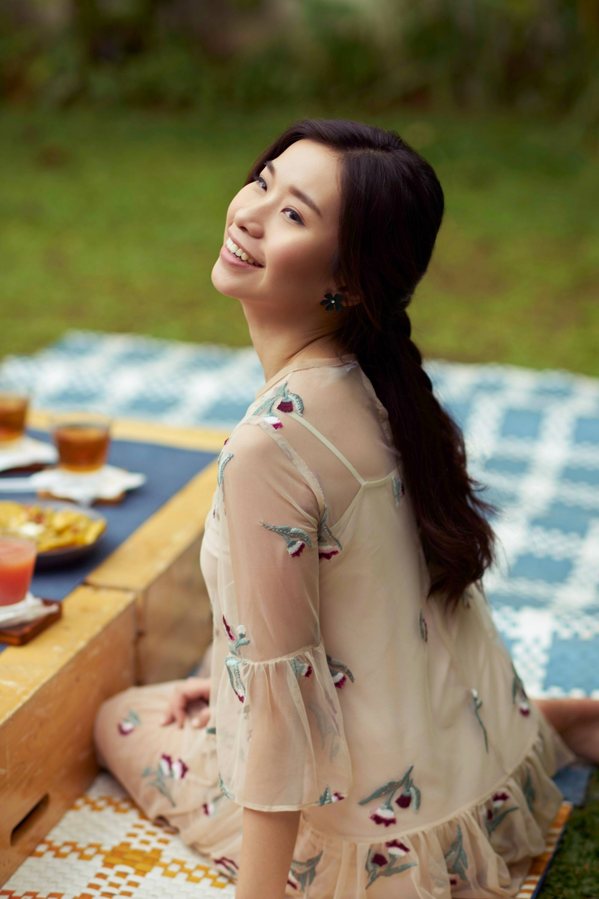Half ponytail: Asian woman with long dark hair in braided half updo wearing a dress and sitting on a picnic mat