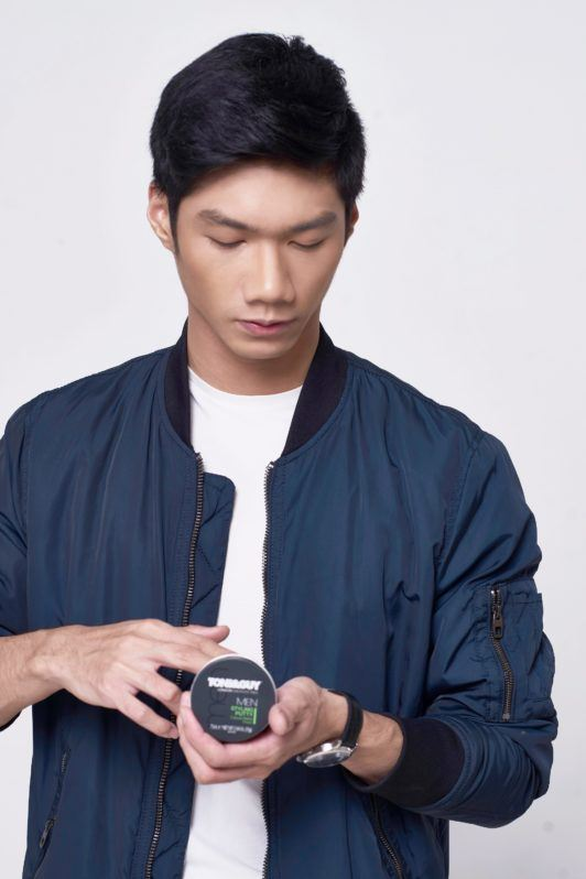 How to style short hair for men: Asian man with short black hair wearing a blue jacket and white shirt opening a can of hair putty