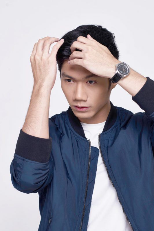 How to style short hair for men: Asian man styling her short black hair wearing blue jacket and white shirt