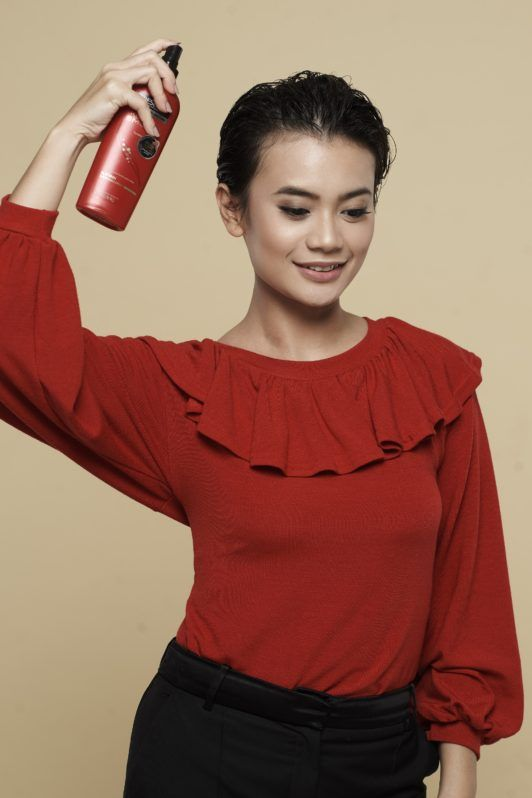 How to style wet to dry pixie: Asian woman spraying heat protectant on her short black hair