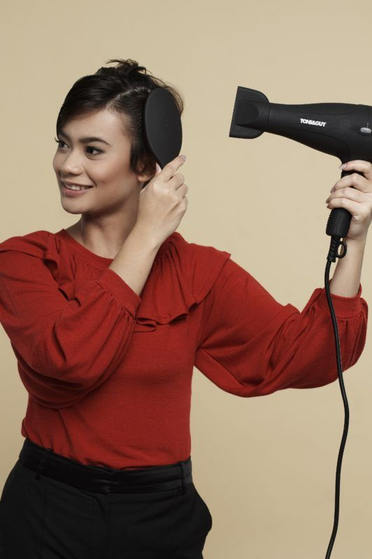 How to style wet to dry pixie: Asian woman blow drying and brushing her short black hair