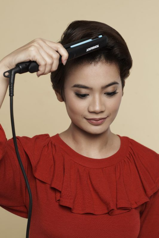 How to style wet to dry pixie cut: Closeup shot of an Asian woman ironing her short black hair
